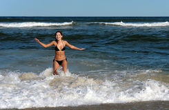 Smiling young woman playing with waves Stock Photography