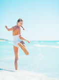 Smiling young woman playing with waves on beach Stock Photo