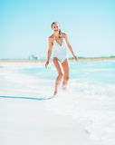 Smiling young woman playing with waves on beach Royalty Free Stock Photo