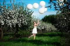Smiling young woman playing with white balloons royalty free stock photography