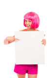 Smiling young woman pointing at blank board. Portrait of a pink haired smiling young woman pointing at blank board. Three quarter length studio shot isolated on Royalty Free Stock Photo