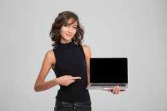 Smiling young woman pointing on blank laptop computer screen. Smiling young pretty curly woman pointing on blank laptop computer screen royalty free stock photo