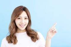 Young woman pointing at blue background royalty free stock image