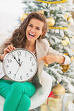 Smiling young woman pointing on clock in front of christmas tree Royalty Free Stock Photo
