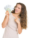 Smiling young woman pointing on euros stock image