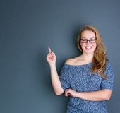 Smiling young woman pointing finger Royalty Free Stock Images