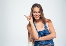 Smiling young woman pointing finger away Stock Photography