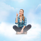 Smiling young woman pointing finger up Stock Image