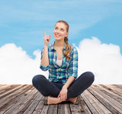 Smiling young woman pointing finger up Royalty Free Stock Image