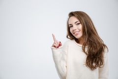 Smiling young woman pointing finger up Stock Photos
