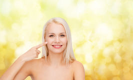 Smiling young woman pointing at her cheek Stock Photography