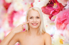 Smiling young woman pointing at her cheek Royalty Free Stock Images