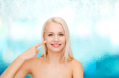 Smiling young woman pointing at her cheek Royalty Free Stock Photography