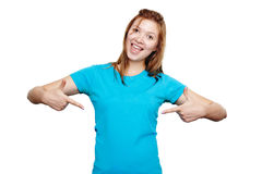 Smiling young woman pointing at herself. T-shirt design. T-shirt design concept. Excited happy young woman pointing to empty space on her blue t-shirt with both stock image