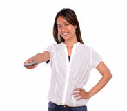 Smiling young woman pointing with remote control Stock Photography