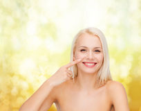 Smiling young woman pointing to her nose Stock Photography