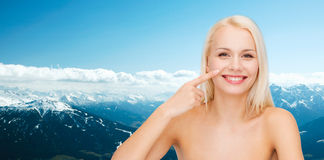 Smiling young woman pointing to her nose Royalty Free Stock Photography