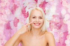 Smiling young woman pointing to her nose Royalty Free Stock Photos