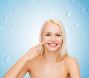 Smiling young woman pointing to her nose Stock Images