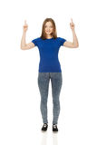Smiling young woman pointing up. Happy beautiful young woman pointing up Stock Photos
