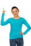 Smiling young woman pointing up. Stock Photography