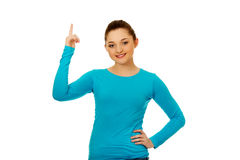 Smiling young woman pointing up. Royalty Free Stock Photography