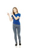 Smiling young woman pointing up. royalty free stock images