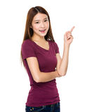 Smiling young woman pointing upwards Stock Images