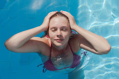 Smiling young woman in the pool with closed eyes. Concept rest,. Summer, relaxation, pleasure, pleasure. View from above royalty free stock images