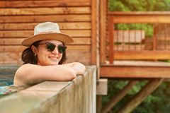 Smiling young woman in pool. With hat and sunglasses Stock Photography