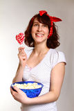 Smiling young woman with popcorn and lollipopg  on a gra Royalty Free Stock Photo