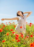 Smiling young woman on poppy field Royalty Free Stock Photos