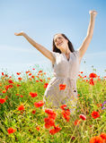 Smiling young woman on poppy field Royalty Free Stock Image