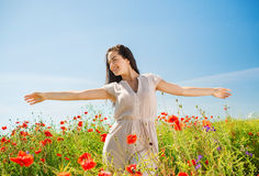 Smiling young woman on poppy field Royalty Free Stock Photography
