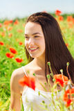 Smiling young woman on poppy field Royalty Free Stock Images