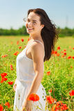 Smiling young woman on poppy field Stock Image
