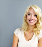 Smiling young woman portrait. Smiling blonde caucasian woman looking up on grey background Stock Photos
