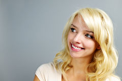 Smiling young woman portrait. Portrait of smiling young blonde woman looking to the side on grey background Stock Images