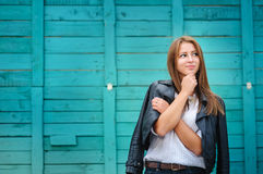 Smiling young woman posing against wooden fence. Smiling young woman posing against turquoiuse wooden fence Royalty Free Stock Photos