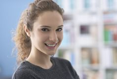 Smiling young woman posing at home. Young attractive curly woman posing at home and smiling at camera, bookshelves on the background stock images