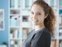 Smiling young woman posing at home. Young attractive curly woman posing at home and smiling at camera, bookshelves on the background royalty free stock images
