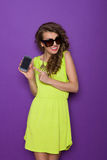 Smiling young woman posing with smart phone Stock Image