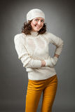 Smiling young woman posing in a studio wearing in a sweater and Royalty Free Stock Image