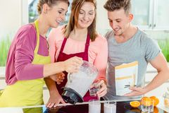 Woman pouring fresh smoothie to her friends royalty free stock photography