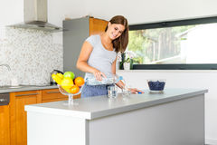 Smiling young woman pouring mineral water into glasses. In kitchen Royalty Free Stock Images