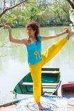 Smiling young woman practice yoga balance posture  outdoor by the lake healthy lifestyle concept. Full body shot ghf stock photos