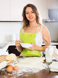 Smiling young woman preparing cakes Stock Photography