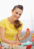 Smiling young woman preparing Easter red eggs Royalty Free Stock Photos