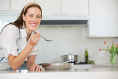 Smiling young woman preparing food in kitchen stock images
