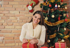 Smiling young woman with present box on Christmas tree backgroun Stock Photography